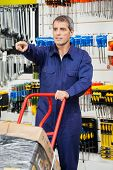 Mature worker in overalls with trolley pointing in hardware shop