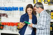 Happy couple analyzing product in hardware store
