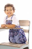 happy toddler sitting in a desk isolated