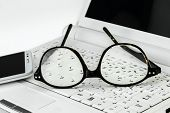 Eyeglasses  And Cell Phone On A Small Laptop