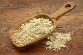 a rustic scoop of rice bran against grunge wood