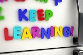 The words keep learning written on a refrigerator door with magnet letters