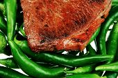 meaty food : roasted red meat steak over green hot chili peppers on a white back