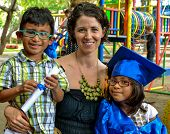 picture of graduation  - A kindergarten graduate poses in front of her playground with her brother and adopted mom in her blue graduation gown with her diploma - JPG