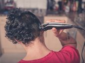 picture of clippers  - A young man is using hair clippers to give himself a haircut in his kitchen - JPG