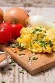 stock photo of scrambled eggs  - Vertical photo of scrambled eggs mixed with chive with salt pieces around placed on chopping board - JPG