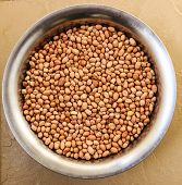 picture of groundnut  - Freshly roasted groundnut or peanut kept on a vessel on a plain background - JPG