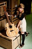 Beautiful Young Woman With A Classical Guitar In A Warehouse With Boxes Like Scenario poster