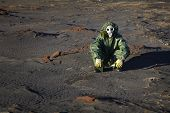 stock photo of scoria  - A man in protective clothing sitting in the desert - JPG