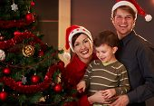 pic of nuclear family  - Happy parents holding small child at christmas tree boy pointing at tree - JPG