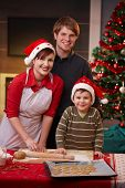 picture of nuclear family  - Happy parents with small child baking christmas cake together smiling at camera - JPG