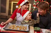stock photo of nuclear family  - Small son helping dad tasting christmas cake at table mother watching laughing - JPG