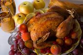 picture of turkey dinner  - roasted chicken or turkey garnished with lemon cranberry apples tomatoes bread and wine - JPG