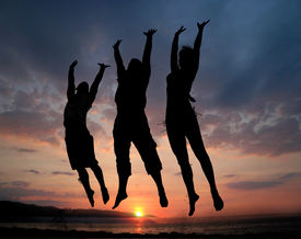 stock photo of beach party  - three people silhouettes jumping on the beach - JPG
