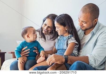 poster of Multiethnic family playing with happy baby son at home. Parent and children relaxing together on the