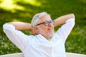 old age, retirement and people concept - happy senior man in glasses sitting and relaxing outdoors poster
