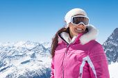 Happy woman with mask for snowboarding looking away with mountains covered by snow in background. Sm poster