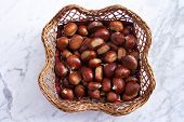 Wicker Basket Of Chestnuts On A Marble Table