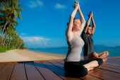 An attractive young woman and man doing yoga on a jetty with the blue ocean and another island behin