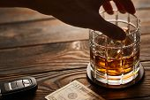 Mans hand reaching to glass of whiskey or alcohol drink with ice cubes and car key on rustic wooden poster
