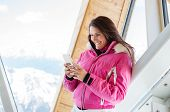 Young woman in warm jacket using mobile phone. Cheerful woman in pink jacket reading message while t poster