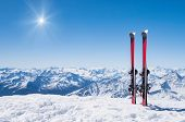 Pair of skis in snow with copy space. Red skis standing in snow with winter mountains in background. poster