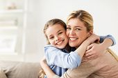people and family concept - happy smiling girl with mother hugging on sofa at home poster