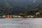 Gate Temple By The Beach. Far-away Look Of Itsukushima Shrine In Miyajima Island, Japan. The Gate Is poster
