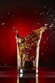 Close-up Of Glass With Whiskey Splash.on Red Background.concept Alcohol Splash poster