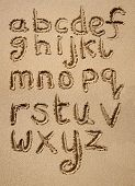 The Alphabet Written In Sand On A Beach.
