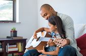 Little girl and black father playing guitar and smiling while sitting on couch at home. African dad  poster