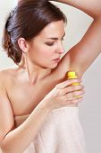 beautiful woman applying roll-on antiperspirant