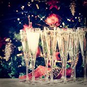 Filling Up Glasses For Party. Glasses Of Champagne With Christmas Tree Background And Sparkles. Holi poster