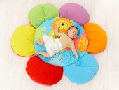 picture of playmate  - Baby lying on flower shape playmat - JPG