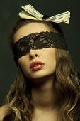 Mooie sexy vrouw hoofd-gekleed met dollars kijken door zwarte opengewerkte kant in de duisternis