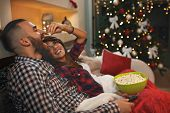 Couple in love at Christmas eve enjoy with popcorn while watching tv poster