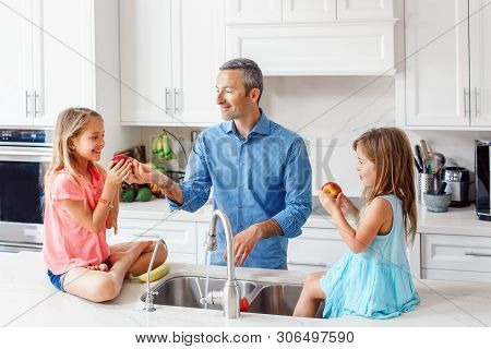 poster of Caucasian Father Dad Gives Children Daughters Fresh Fruits To Eat. Happy Family In Kitchen Eating. O