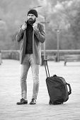 Looking For Accommodation. Man Bearded Hipster Travel With Big Luggage Bag Wait For Taxi Bring Him T poster