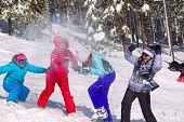 Girls having snowball fight in snow in winter background