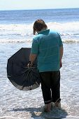 Teen With Umbrella Facing The Ocean