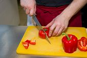 Tough Guy Cutting Paprika At Kitchen. Chefs Hands With Knife Cutting Red Paprika On Cutting Board Fo poster