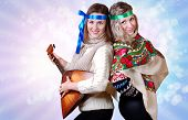 stock photo of mummer  - Two russian beauties with folk attributes on the shining light background - JPG