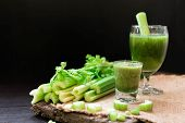Blended Celery Juice In Welcome Drink Glass And Bunch Of Fresh Celery Stalk On Wooden Table With Lea poster