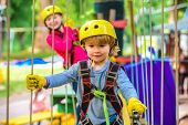 Happy Little Boyn Calling While Climbing High Tree And Ropes. Eco Resort Activities. Go Ape Adventur poster