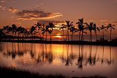 stock photo of fish pond  - Waikoloa Sunset on the Island of Hawaii in front of ancient fish ponds and coconut tree covered beach - JPG
