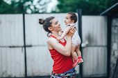 Beautiful Mother And Baby Outdoors On The Yard Of House. Beauty Mum And Her Baby Child One Year Old poster