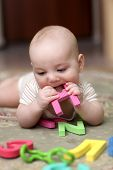 stock photo of love bite  - The baby boy biting letter on a carpet at home - JPG