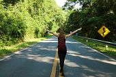 Female Carefree Backpacker In The Middle Of The Forest On Asphalt Road. Tourist Traveler Feelings Fr poster