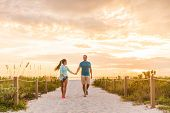 Happy young couple in love walking on romantic beach stroll at sunset. Lovers holding hands on Flori poster