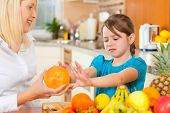 Healthy eating - mother and child sitting in the kitchen with different kinds of fruits, the kid doe